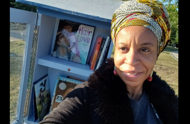 """Photo of a Black woman with a yellow, white, black, and red head wrap standing in front of a blue hutch that has books inside. The front cover of the book """"Hair Love,"""" featuring a cartoon depction of a Black man and little girl looking at one another, is visible."""