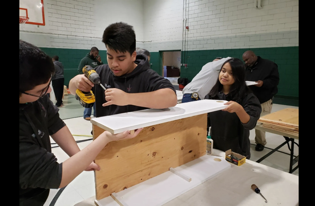 Photo of three teens putting together a wooden box that will be used for Little Free Library boxes. They are in what seems to be a gymnasium that is painted white on the top half and a dark green below. There is a white and red basketball net visible in the upper left hand portion of the photo.