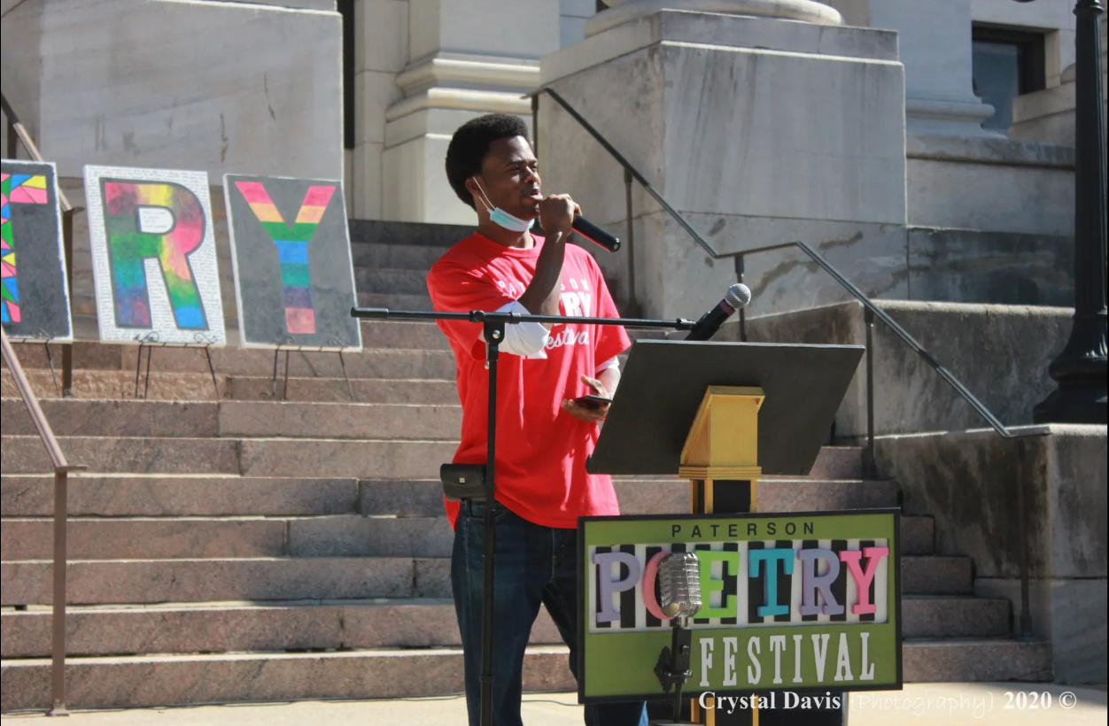 Photo of a young Black man in a salmon-colored tshirt is holding a microphone and speaking from behind a pedastol with a plackard that says Paterson Poetry Festival. The letters TRY are displayed behind him in rainbow colors on top of tan stone steps.